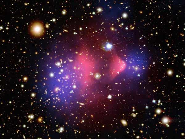 Столкновение двух скоплений галактик. Наложены три изображения: оптическое (галактики), рентгеновское (розовый цвет — горячий газ) и реконструкция распределения массы (синий цвет), сделанная с помощью гравитационного линзирования. Галактики с их звездами свободно прошли друг через друга и с ними — облака темной материи, в которых заключена основная масса (два синих облака). А газ скоплений, который по массе на порядок превосходит звезды галактик, неупруго провзаимодействовал — облака газа отстали от своих скоплений.